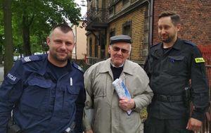 Policjanci z uśmiechniętym Seniorem, który cieszy się z tego, że bezpiecznie wróci do domu.